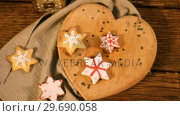 Купить «Christmas gingerbread cookies on wooden table», видеоролик № 29690058, снято 31 августа 2016 г. (c) Wavebreak Media / Фотобанк Лори