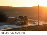 Купить «Salo, Finland - November 24, 2018: Scania vehicle carrier hauls new trucks at the warm light of sunset at bypass road on winter afternoon in Finland.», фото № 29690446, снято 24 ноября 2018 г. (c) age Fotostock / Фотобанк Лори