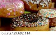 Close-up of tasty doughnuts with sprinkles. Стоковое видео, агентство Wavebreak Media / Фотобанк Лори