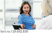 Купить «Female doctor interacting over digital tablet with a pregnant woman», видеоролик № 29692830, снято 25 августа 2016 г. (c) Wavebreak Media / Фотобанк Лори