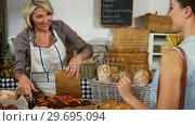 Купить «Female staff assisting woman in purchasing doughnut at bakery section», видеоролик № 29695094, снято 4 октября 2016 г. (c) Wavebreak Media / Фотобанк Лори