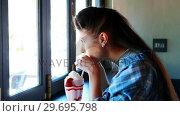 Купить «Happy woman looking through window while drinking milkshake», видеоролик № 29695798, снято 14 ноября 2016 г. (c) Wavebreak Media / Фотобанк Лори