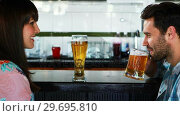 Купить «Happy couple interacting while having beer», видеоролик № 29695810, снято 14 ноября 2016 г. (c) Wavebreak Media / Фотобанк Лори