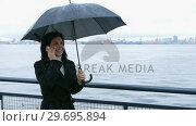 Купить «Woman holding umbrella and talking on mobile phone», видеоролик № 29695894, снято 21 февраля 2019 г. (c) Wavebreak Media / Фотобанк Лори