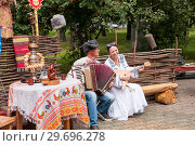 Купить «Russia, Khabarovsk, August 18, 2018: a man and a woman in Russian-national costumes play the accordion and balalaika», фото № 29696278, снято 18 августа 2018 г. (c) Катерина Белякина / Фотобанк Лори