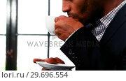 Купить «Close-up of businessman drinking cup of coffee», видеоролик № 29696554, снято 21 ноября 2016 г. (c) Wavebreak Media / Фотобанк Лори