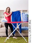 Купить «Young beautiful woman ironing at home», фото № 29697862, снято 30 октября 2018 г. (c) Elnur / Фотобанк Лори