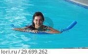 Купить «Beautiful woman swimming with inflatable tube in pool», видеоролик № 29699262, снято 29 ноября 2016 г. (c) Wavebreak Media / Фотобанк Лори