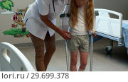 Купить «Female doctor assisting girl to walk with crutches», видеоролик № 29699378, снято 5 ноября 2016 г. (c) Wavebreak Media / Фотобанк Лори