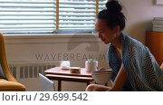 Купить «Beautiful woman having cereal while using laptop», видеоролик № 29699542, снято 21 января 2017 г. (c) Wavebreak Media / Фотобанк Лори