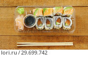 Купить «Sushi rolls with salmon in plastic container», видеоролик № 29699742, снято 8 декабря 2016 г. (c) Wavebreak Media / Фотобанк Лори