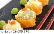Купить «Sushi served on tray with chopsticks», видеоролик № 29699870, снято 8 декабря 2016 г. (c) Wavebreak Media / Фотобанк Лори