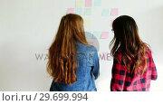 Купить «Female executives discussing over sticky notes», видеоролик № 29699994, снято 23 октября 2016 г. (c) Wavebreak Media / Фотобанк Лори
