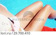 Купить «Sexy woman in bikini sitting on the pool side with her legs in water», видеоролик № 29700410, снято 1 февраля 2017 г. (c) Wavebreak Media / Фотобанк Лори