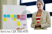 Купить «Female executive giving presentation to colleague in office», видеоролик № 29700470, снято 31 января 2016 г. (c) Wavebreak Media / Фотобанк Лори