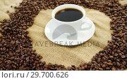 Купить «Cup of coffee surrounded with roasted beans», видеоролик № 29700626, снято 6 октября 2016 г. (c) Wavebreak Media / Фотобанк Лори