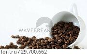 Купить «Roasted coffee beans spilling out of cup», видеоролик № 29700662, снято 6 октября 2016 г. (c) Wavebreak Media / Фотобанк Лори