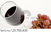 Купить «Close-up of red bunch of grapes with glass of red wine», видеоролик № 29700830, снято 19 декабря 2016 г. (c) Wavebreak Media / Фотобанк Лори
