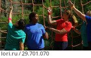 Купить «Female trainer assisting women in climbing net during obstacle course», видеоролик № 29701070, снято 16 марта 2017 г. (c) Wavebreak Media / Фотобанк Лори