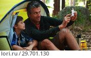 Купить «Father and son taking a selfie on mobile phone outside tent», видеоролик № 29701130, снято 2 марта 2017 г. (c) Wavebreak Media / Фотобанк Лори