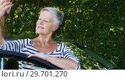Купить «Senior woman talking on mobile phone near car», видеоролик № 29701270, снято 3 февраля 2017 г. (c) Wavebreak Media / Фотобанк Лори