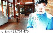 Купить «Schoolboy witting while walking in corridor», видеоролик № 29701470, снято 19 ноября 2016 г. (c) Wavebreak Media / Фотобанк Лори