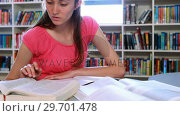 Купить «Attentive schoolgirl doing homework in library», видеоролик № 29701478, снято 19 ноября 2016 г. (c) Wavebreak Media / Фотобанк Лори