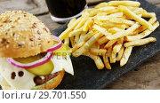 Купить «Hamburger, french fries and cold drink on slate board», видеоролик № 29701550, снято 13 января 2017 г. (c) Wavebreak Media / Фотобанк Лори