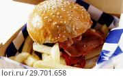 Купить «Hamburger and french fries in a take away container on table», видеоролик № 29701658, снято 13 января 2017 г. (c) Wavebreak Media / Фотобанк Лори
