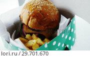 Купить «Hamburger and french fries on table», видеоролик № 29701670, снято 13 января 2017 г. (c) Wavebreak Media / Фотобанк Лори