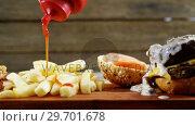 Купить «Ketchup being squeezed over hamburger on tray», видеоролик № 29701678, снято 13 января 2017 г. (c) Wavebreak Media / Фотобанк Лори