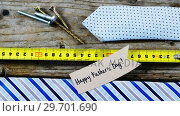 Купить «Happy fathers day card, tie, screw, measuring tape on wooden plank», видеоролик № 29701690, снято 13 января 2017 г. (c) Wavebreak Media / Фотобанк Лори