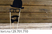 Купить «Bow tie, spectacles and fake mustache arranged on wooden plank», видеоролик № 29701710, снято 13 января 2017 г. (c) Wavebreak Media / Фотобанк Лори