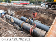 Купить «Repair work of heating duct. The workers, welders made by electric welding on large iron pipes at a depth of excavated trench», фото № 29702202, снято 1 октября 2017 г. (c) FotograFF / Фотобанк Лори