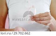 Mid-section of woman holding breast cancer awareness ribbon. Стоковое видео, агентство Wavebreak Media / Фотобанк Лори