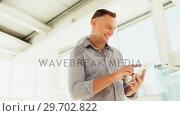 Купить «Happy executive using digital tablet», видеоролик № 29702822, снято 26 марта 2017 г. (c) Wavebreak Media / Фотобанк Лори