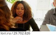 Купить «Team of executives interacting with each other while working in the office», видеоролик № 29702826, снято 26 марта 2017 г. (c) Wavebreak Media / Фотобанк Лори
