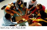 Купить «Group of happy executives having pizza in office», видеоролик № 29702834, снято 26 марта 2017 г. (c) Wavebreak Media / Фотобанк Лори