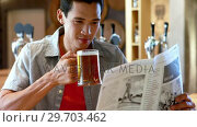 Купить «Man having beer while reading newspaper in a restaurant 4k», видеоролик № 29703462, снято 28 марта 2017 г. (c) Wavebreak Media / Фотобанк Лори
