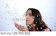 Купить «Smiling woman blowing confetti 4k», видеоролик № 29703922, снято 22 мая 2017 г. (c) Wavebreak Media / Фотобанк Лори