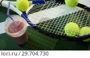 Купить «Milkshake and sports equipment in tennis court 4k», видеоролик № 29704730, снято 6 апреля 2017 г. (c) Wavebreak Media / Фотобанк Лори
