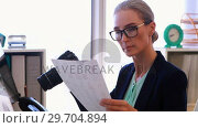 Купить «Female executive reviewing captured photograph at her desk 4k», видеоролик № 29704894, снято 19 марта 2017 г. (c) Wavebreak Media / Фотобанк Лори