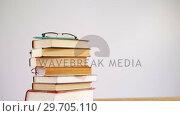 Купить «Spectacles and pencil on book stack 4k», видеоролик № 29705110, снято 26 мая 2017 г. (c) Wavebreak Media / Фотобанк Лори
