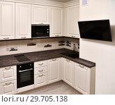 Купить «Fragment of beige kitchen and tv on the wall», фото № 29705138, снято 29 октября 2018 г. (c) Володина Ольга / Фотобанк Лори