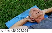 Купить «Senior man lying on exercise mat in garden 4k», видеоролик № 29705354, снято 28 апреля 2017 г. (c) Wavebreak Media / Фотобанк Лори