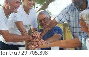 Купить «Happy volunteers forming handstack with each other 4k», видеоролик № 29705398, снято 28 апреля 2017 г. (c) Wavebreak Media / Фотобанк Лори