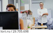 Купить «Smiling executive standing with arms crossed while colleagues talking on headset 4k», видеоролик № 29705698, снято 19 марта 2017 г. (c) Wavebreak Media / Фотобанк Лори