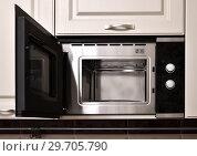 Купить «Open empty microwave in the kitchen cupboard», фото № 29705790, снято 29 октября 2018 г. (c) Володина Ольга / Фотобанк Лори