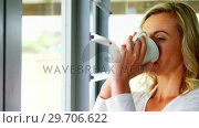 Купить «Woman with coffee cup by window 4k», видеоролик № 29706622, снято 24 марта 2017 г. (c) Wavebreak Media / Фотобанк Лори