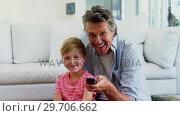 Купить «Father and son watching television in living room 4k», видеоролик № 29706662, снято 24 марта 2017 г. (c) Wavebreak Media / Фотобанк Лори
